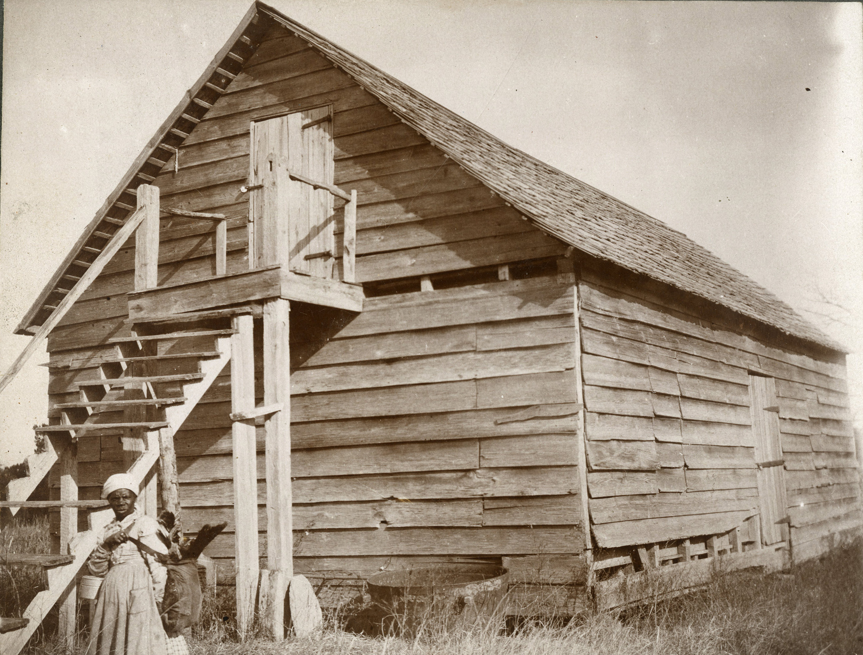 Photograph of a Woman Gesturing in Front of a Rice Granary, Wantoot plantation